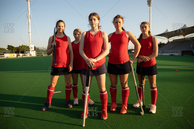 Front view of a Caucasian female field hockey players, training before a game, standing on a hockey pitch, holding hockey sticks, looking at camera, on a sunny day