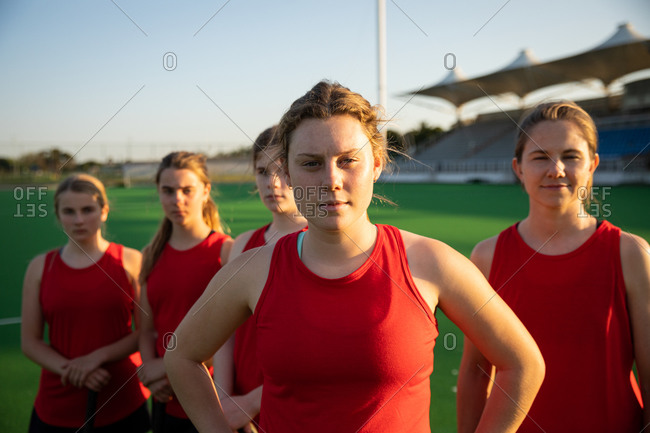 Portrait of a Caucasian female field hockey player, training before a game, standing on a hockey pitch, looking at camera, with her teammates standing in a row behind her on a sunny day