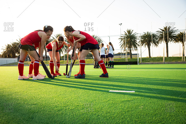 Side view of two teams of female Caucasian field hockey players, preparing before a game, huddling, motivating each other, on a sunny day