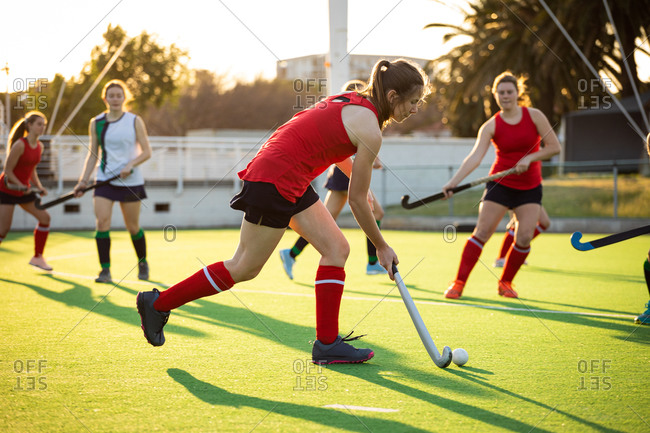 Side view of a Caucasian female field hockey player, during a field hockey game, running with a ball, holding a hockey stick, with her teammates and opponents in the background, on a sunny day