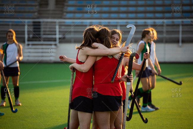 Side view of a team of female Caucasian field hockey players, during a field hockey game, celebrating a goal, with disappointed opponents standing in the background, on a sunny day
