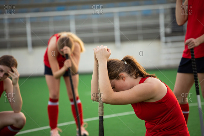 Side view of a Caucasian female field hockey player, after a field hockey game, kneeling, leaning her head on a hockey stick with disappointment, with her teammates in the background, on a sunny day