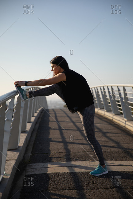 Side view of a fit Caucasian woman with long dark hair wearing sportswear exercising outdoors in the city on a sunny day with blue sky, warming up, stretching her leg,