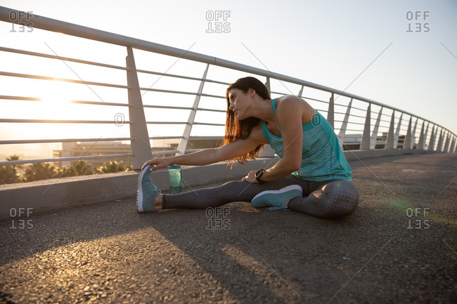 Side view of a fit Caucasian woman with long dark hair wearing sportswear exercising outdoors in the city on a sunny day with blue sky, warming up, sitting and stretching her leg,