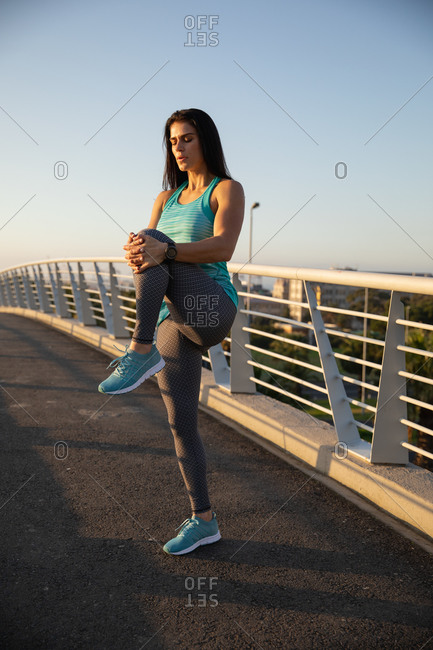 Front view of a fit Caucasian woman with long dark hair wearing sportswear exercising outdoors in the city on a sunny day with blue sky, warming up, stretching her leg,