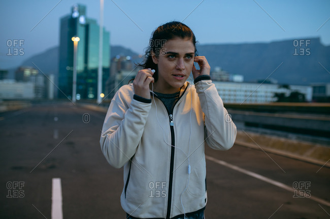 Front view of a fit Caucasian woman with long dark hair wearing sportswear exercising outdoors in the city in the evening, running putting her earphones on, with urban buildings in the background.