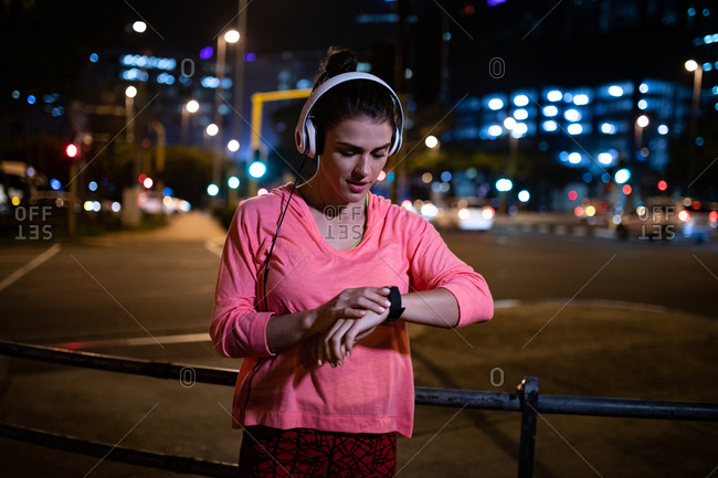 Front view of a fit Caucasian woman with long dark hair wearing sportswear exercising outdoors in the city in the evening, standing checking her smartwatch with headphones on with urban buildings in the background.