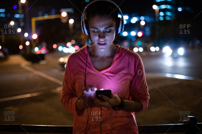 Front view of a fit Caucasian woman with long dark hair wearing sportswear exercising outdoors in the city in the evening, taking a break from her workout standing with headphones using a smartphone with urban buildings in the background.
