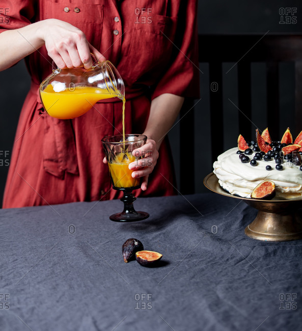 Woman pours orange juice next to a cake