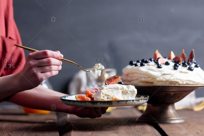 Woman eating a Pavlova cake