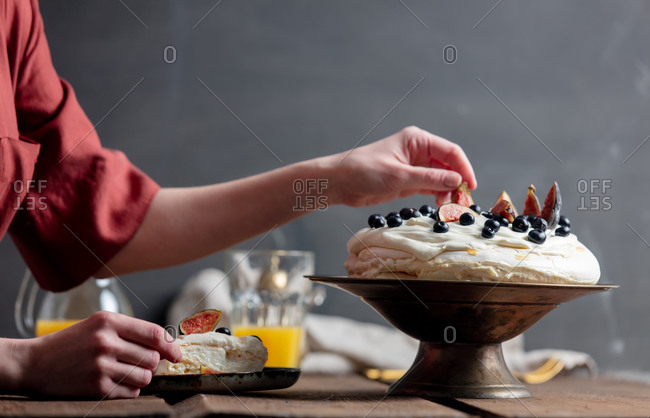 Woman decorating a beautiful Pavlova cake