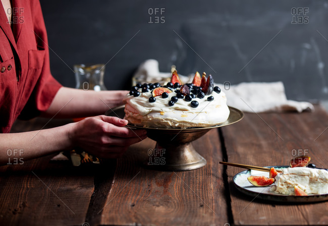 Woman holds beautiful Pavlova cake over a table