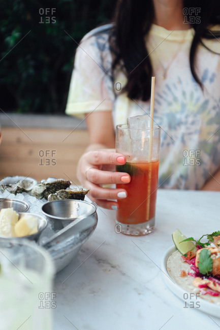Woman with colorful fingernails having a cocktail and appetizers