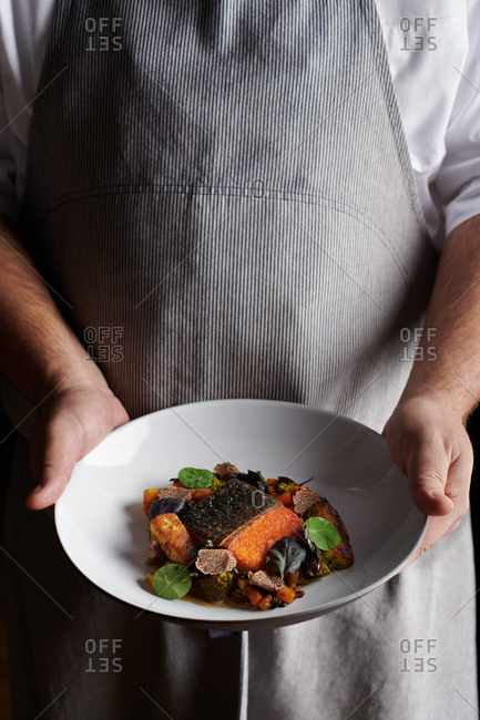 Chef holding artic char dish with truffles, micro greens and vegetables