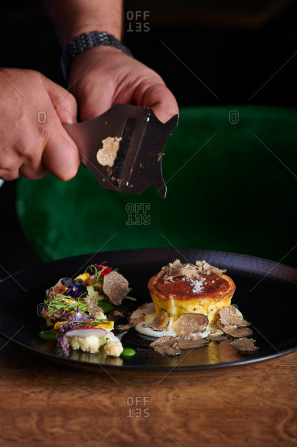 Chef preparing corn cake on a black plate with cheese oozing out with micro greens on the side