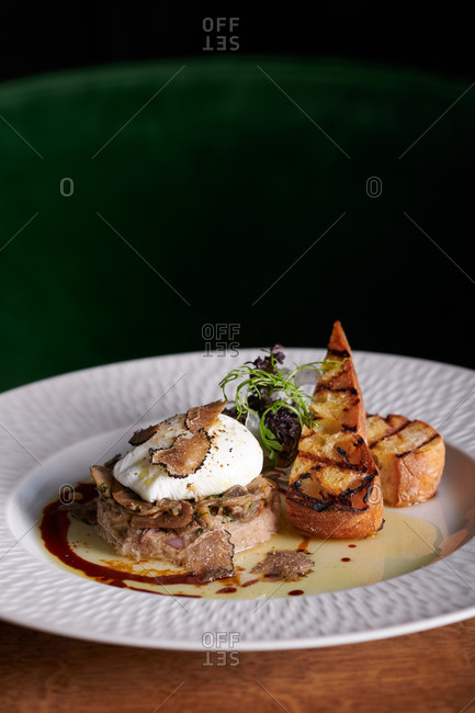 A dish featuring truffle shavings, poached egg on mushrooms and crostini in a restaurant in Sacramento, California