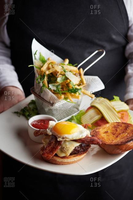 Cheeseburger with egg served open faced showing bacon and truffle fries, being presented by a server in a restaurant in Truckee, California