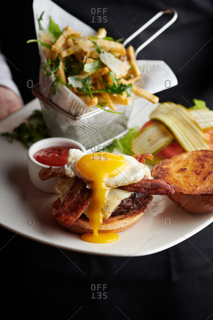 Cheeseburger with egg yolk dripping served open faced showing bacon and truffle fries, being presented by a server in a restaurant in Truckee, California