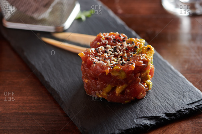 Tuna Poke on a small black piece of slate with sesame seeds and avocado mixed in