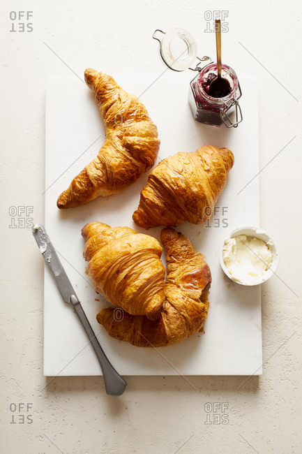 Croissants with jam and butter on marble cutting board. Morning atmosphere