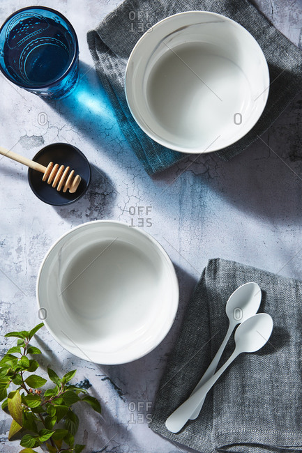 Two white bowls and spoons by blue glass and honey stick