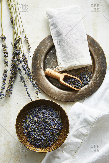 Overhead view of dried lavender being put into a muslin bag