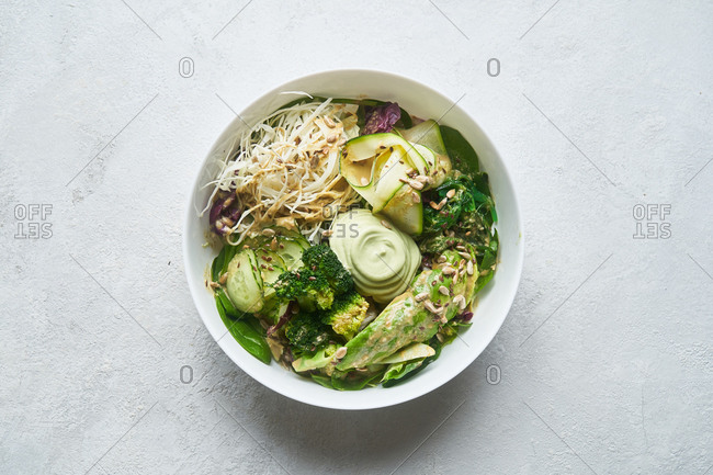 Overhead view of a healthy green salad on light background