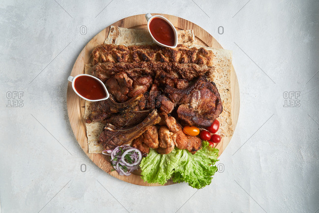 Overhead view of a wooden board filled with meat and sauce on light background