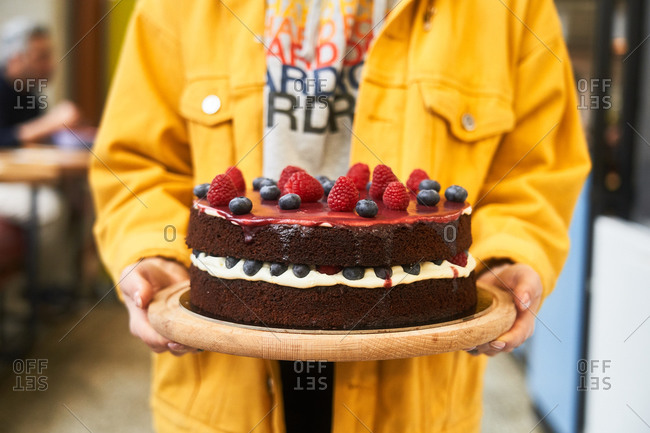 Woman holding a chocolate cake topped with berries