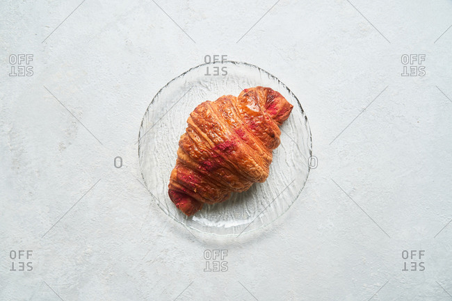 A single croissant on a glass plate