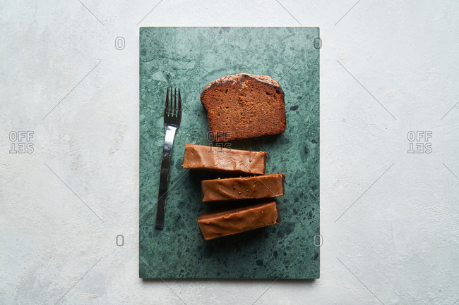 A loaf cake sliced on stone surface