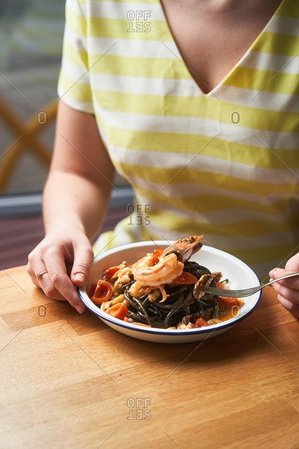 Woman eating a seafood pasta dish in a restaurant