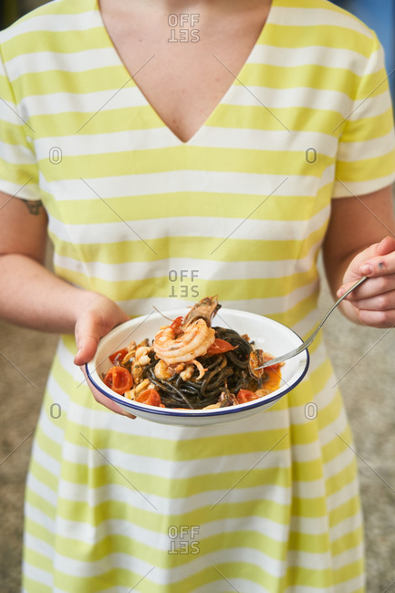 Woman eating a seafood pasta dish