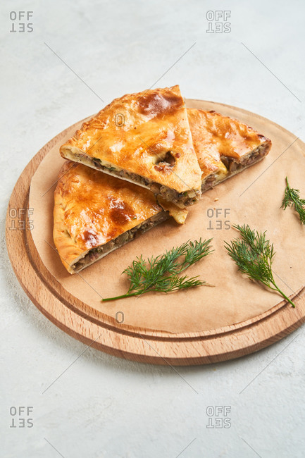 Close up of stuffed flatbread on a round wooden board