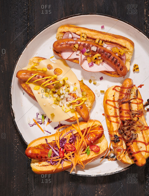Hotdogs in buns served with different toppings like mustard, hot sauce, fried onions and chilies