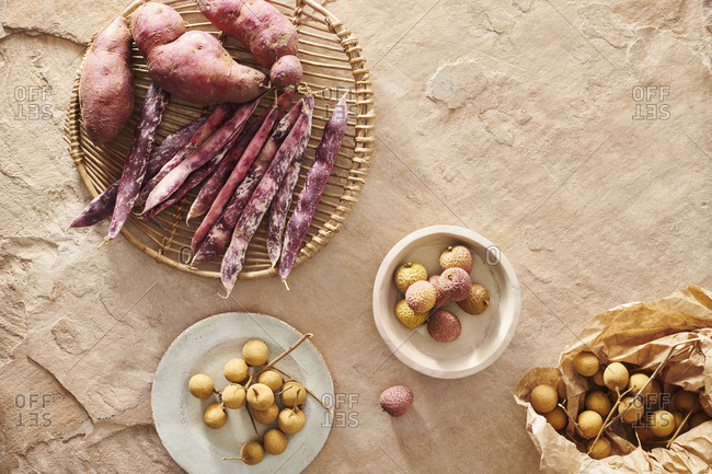 Sweet potatoes, borlotti beans, longan fruit and lychees on a textured stone surface