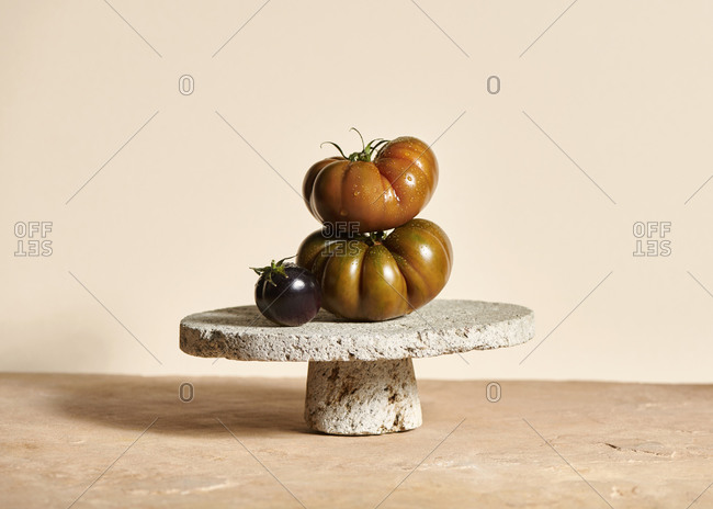 Sicilian tomatoes and a black tomato stacked on a textured concrete pedestal platter