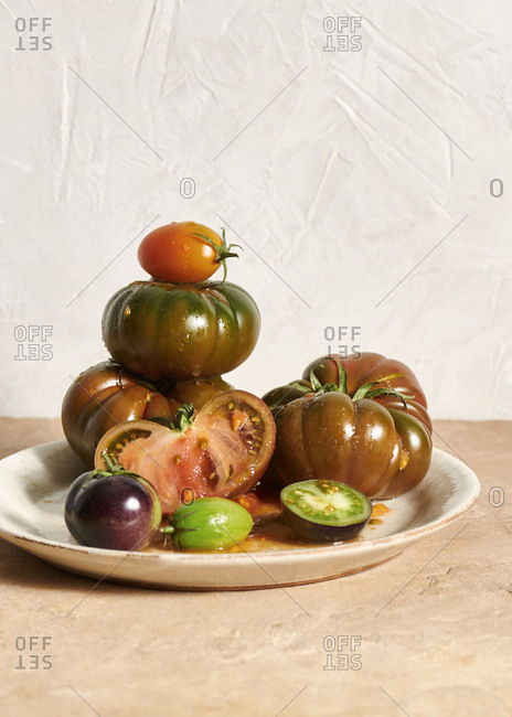 A plate filled with Sicilian tomatoes, black tomatoes and green tomatoes against a plaster wall
