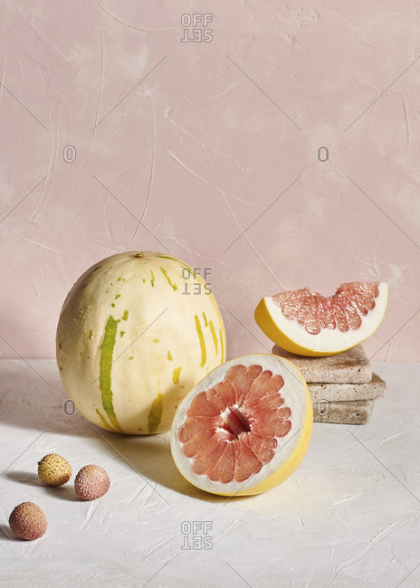 A pomelo fruit, lychees and an unusual speckled melon on textured plaster surfaces