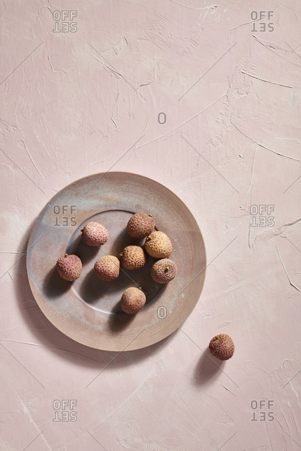 A ceramic plate with lychee fruit on a pink textured plaster surface