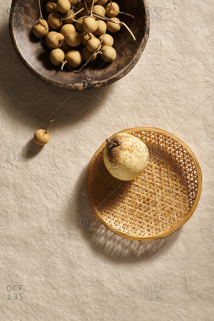 A wooden bowl of longan fruit and an Asian pear in a woven bamboo basket