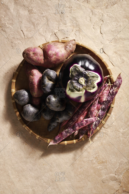 Sweet potatoes, black potatoes, a round aubergine and borlotti beans in a woven bamboo basket