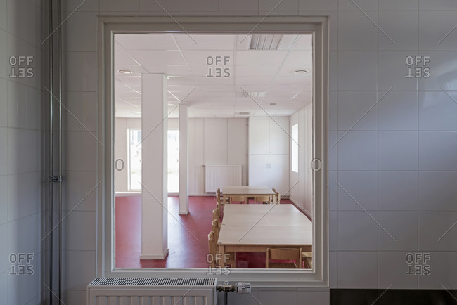 View through window of table and chairs in a school room with red floors