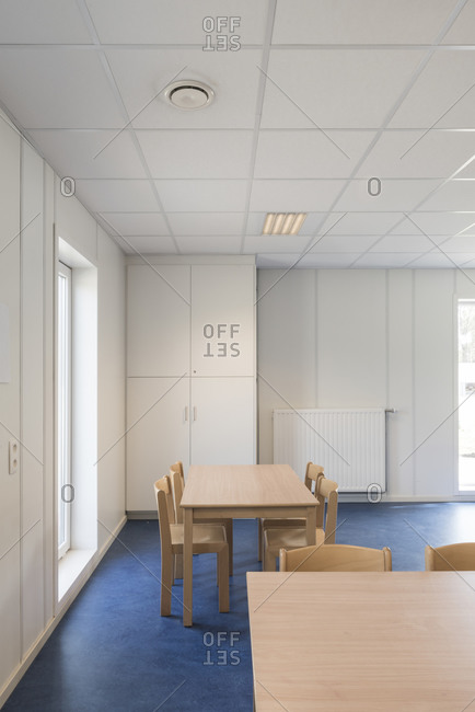 Table and chairs in a school room with blue floors