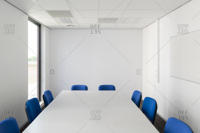Blue chairs around a table inside a conference room