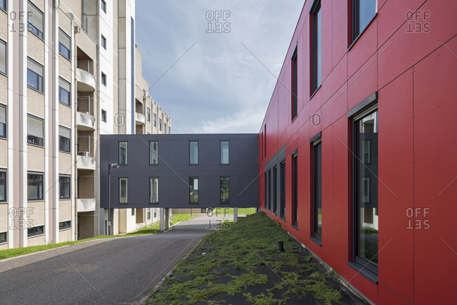 Red building with gray corridor attached to another building in Tongeren, Belgium