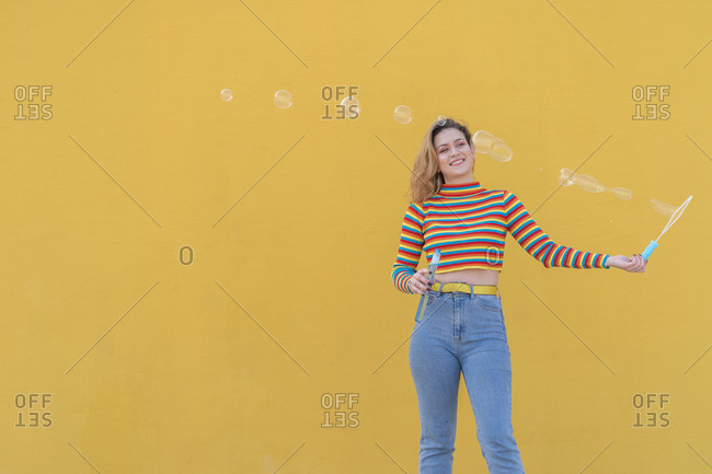 Young woman dressed in a colored striped sweater on a yellow background playing with soap bubbles.