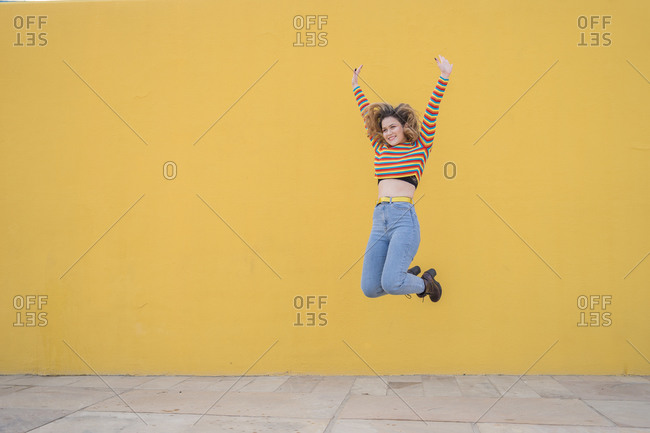 Young woman dressed in a colored striped sweater jumping against yellow background