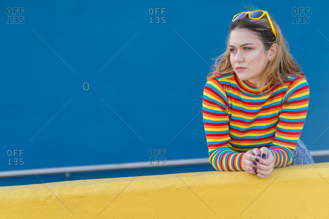Young woman dressed in a colored striped jersey and yellow glasses on a blue background leaning against a yellow wall