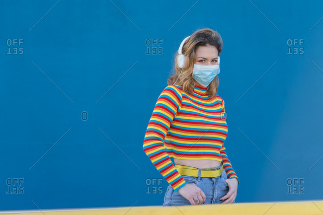Young woman wearing a colored striped sweater on a blue and yellow background with headphones and a medical mask
